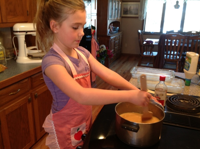Jess is styling in the apron that her great-grandma made her! She's also stirring.