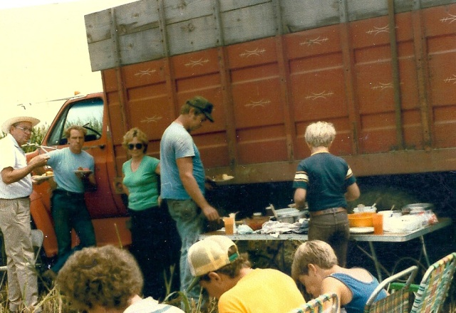 "Found this in my mother-in-law's album so I'm guessing she took it. The 6'6"" guy in the straw rancher hat is my Daddy, doing what he loved.  Eating. Big Boss is next to him, with brother-in-law at the table, then #2 son with #1 son seated on the right next to his buddy and his mom who drove for us.  Now, the question is, where is #3 son?  Probably playing inside the cab?"