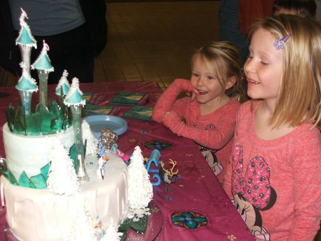 The birthday girl ooohs and aaaahes over cake snow and ice...