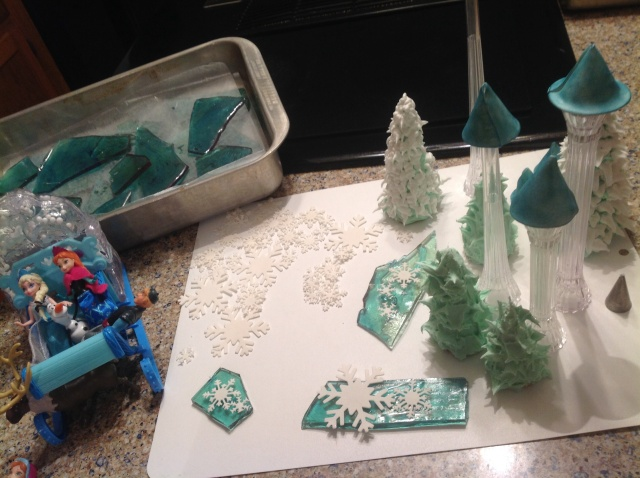 "This shows the green royal icing trees (waffle cones) in the foreground. Background trees have white royal ""snow"" piped over the dried green trees."