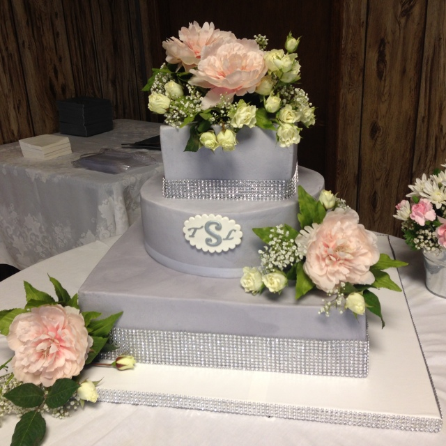 Pale grey icing fresh flowers wedding cake